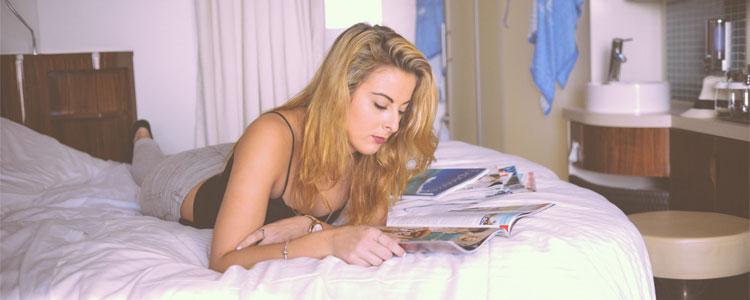 Girl-Reading-Magazine-In-Hotel-Bed