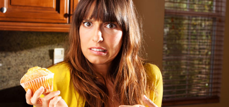 woman-wondering-whether-to-eat-muffin